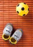 Espadrilles et ballon de football d'enfants sur un plancher en bois dur La vue à partir du dessus Photos stock