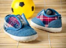 Espadrilles et ballon de football d'enfants sur un plancher en bois dur La vue à partir du dessus Photographie stock