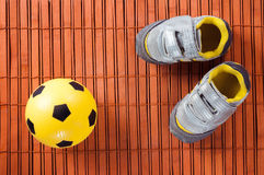 Espadrilles et ballon de football d'enfants sur un plancher en bois dur La vue à partir du dessus Image stock