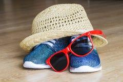 Espadrilles et chapeau de paille lumineux bleus avec les lunettes de soleil rouges Image libre de droits