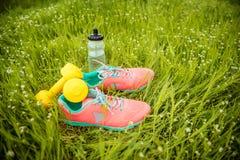 Espadrilles et forme physique d'haltères sur l'herbe verte Images libres de droits