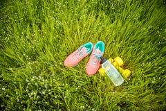 Espadrilles et forme physique d'haltères sur l'herbe verte Photos libres de droits