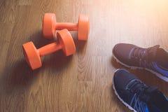 Espadrilles et forme physique d'haltères sur un fond en bois Photographie stock libre de droits