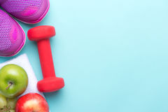 Espadrilles et forme physique d'haltères sur un fond gris Différents outils pour le sport Folâtrez les chaussures et l'eau avec l Photographie stock libre de droits