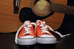 Espadrilles et guitare oranges Photo stock