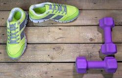 Espadrilles et haltères de sports sur un fond en bois Images stock