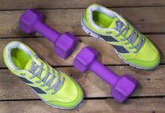 Espadrilles et haltères de sports sur un fond en bois Photos libres de droits