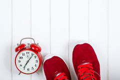 Espadrilles et horloge rouges sur le backgroyund en bois Photo stock