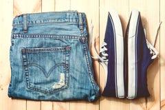 Espadrilles et jeans bleus de la jeunesse sur le fond en bois Image stock