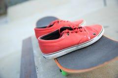 Espadrilles et planche à roulettes au skatepark Photos stock
