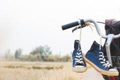 Espadrilles et sac de jeans sur la bicyclette Photographie stock
