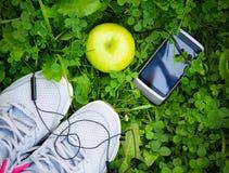 Espadrilles et smartphone avec les écouteurs et la pomme Photos stock