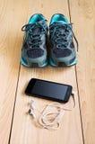 Espadrilles et smartphone de sport avec des écouteurs Photos libres de droits