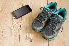 Espadrilles et smartphone de sport avec des écouteurs Images stock