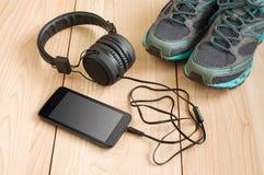 Espadrilles et smartphone de sport avec des écouteurs Photo libre de droits