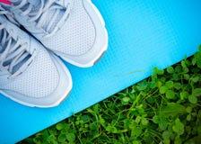Espadrilles et tapis de yoga sur l'herbe verte fraîche Photos libres de droits