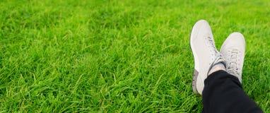Espadrilles femelles sur des jambes dans l'herbe Image stock