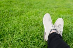 Espadrilles femelles sur des jambes dans l'herbe Photos stock