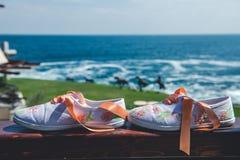 Espadrilles florales nuptiales Détails de mariage de plage devant la mer Image stock