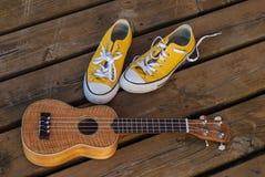 Espadrilles fraîches de jaune de la jeunesse avec l'ukulélé sur le fond en bois Image libre de droits