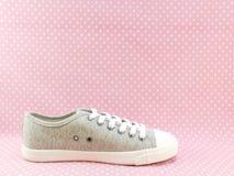 Espadrilles grises de couleur pour la dame avec le fond rose de point de polka Photographie stock libre de droits