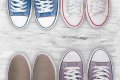 Espadrilles grises et d'autres chaussures sur le fond en bois blanc de plancher, vue supérieure Photos stock