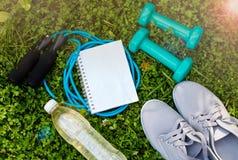 Espadrilles, haltères, bouteille de l'eau, carnet et corde à sauter Photo stock