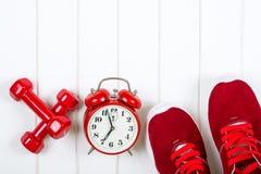 Espadrilles, horloge et haltères rouges sur le backgroyund en bois Photographie stock