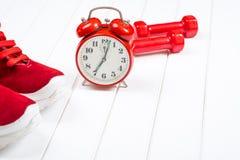 Espadrilles, horloge et haltères rouges sur le backgroyund en bois Photos stock