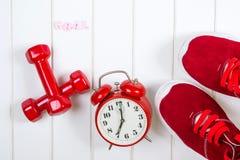 Espadrilles, horloge et haltères rouges sur le backgroyund en bois but Images stock