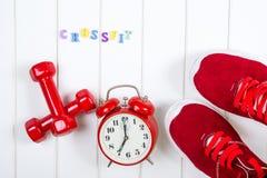 Espadrilles, horloge et haltères rouges sur le backgroyund en bois Crossfit Image stock