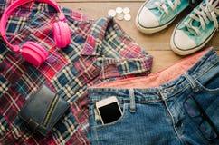 Espadrilles intelligentes de portefeuille d'écouteurs de dispositifs de jeans accessoires sur un plancher en bois Image stock
