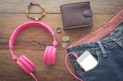 Espadrilles intelligentes de portefeuille d'écouteurs de dispositifs de jeans accessoires sur un plancher en bois Photographie stock libre de droits