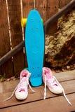 Espadrilles inverses roses près du patin bleu qui se tient près d'en bois Photographie stock libre de droits