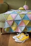Espadrilles jaunes sous le divan avec le fil et le tapis de laine tricoté Images stock