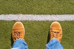 Espadrilles masculines sur l'herbe artificielle Photographie stock libre de droits
