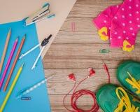 Espadrilles, matériel d'écriture, papier, écouteurs et autre sur en bois Photo stock