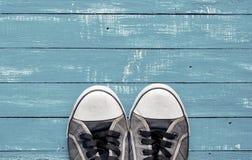 Espadrilles minables bleues du ` s d'hommes vieilles sur une surface en bois bleue Photos libres de droits