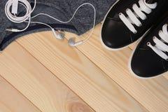 Espadrilles noires avec les dentelles blanches et écouteurs sur un fond en bois Photos libres de droits