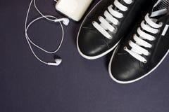Espadrilles noires avec les dentelles blanches et écouteurs sur un fond foncé Photo stock
