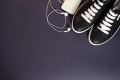 Espadrilles noires avec les dentelles blanches et écouteurs sur un fond foncé Photos libres de droits