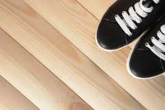 Espadrilles noires avec les dentelles blanches sur un fond en bois Image stock