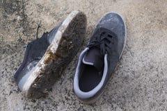 Espadrilles noires boueuses sur le plancher en béton Photographie stock libre de droits