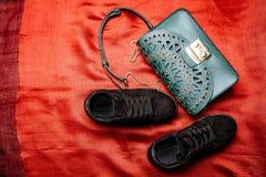 Espadrilles noires de suède et un sac de turquoise avec les modèles et les goujons découpés en métal sur un fond tissé rouge image stock