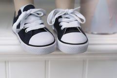 Espadrilles noires et blanches de bébé Photographie stock
