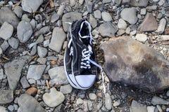 Espadrilles noires et blanches sur des pierres sport de chaussures Photographie stock