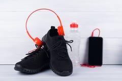 Espadrilles noires et un téléphone portable avec les écouteurs rouges, et une bouteille de l'eau, sur un fond gris Image libre de droits