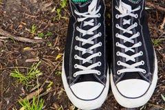Espadrilles noires sur la jambe sur le fond d'herbe Images libres de droits