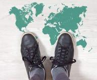Espadrilles noires sur un contour de carte du monde Photographie stock libre de droits
