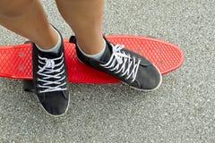 Espadrilles noires sur une planche à roulettes rouge Photo libre de droits